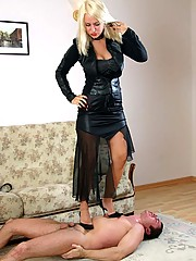 Blonde goddess in black punishes slave and forces him to suck toes